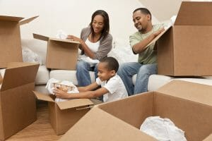 African American family, parents and son, unpacking boxes and moving into a new home, The adults are unpacking crockery and houseware, the child is unpacking a