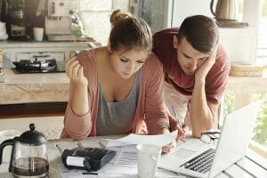 Young married couple with many debts doing paperwork together reviewing their bills planning family budget and calculating finances at kitchen table with papers calculator and laptop computer